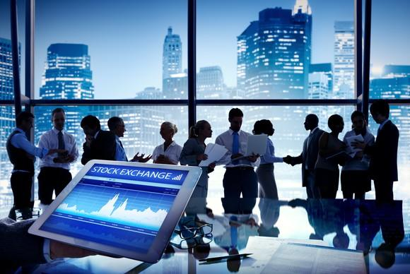 Group of people talking with a stock exchange display in the foreground.