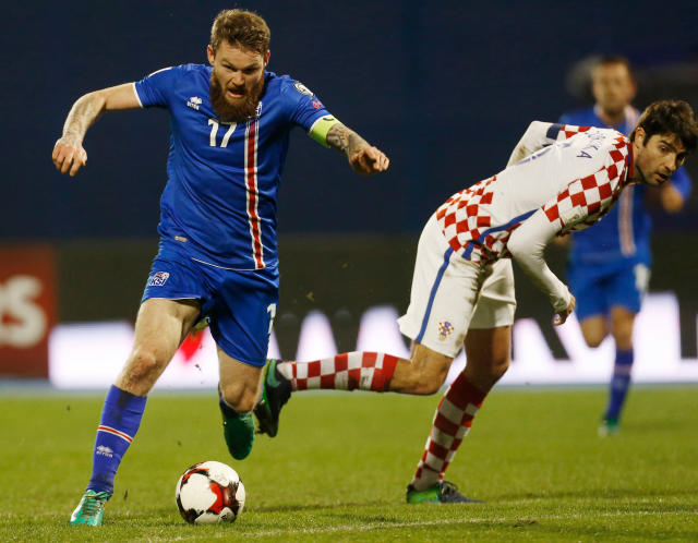FILE - In this Saturday, Nov. 12, 2016 file photo, Iceland's Aron Gunnarsson, left, is challenged by Croatia's Vedran Corluka during the World Cup Group I qualifying soccer match between Croatia and Iceland, at Maksimir stadium in Zagreb, Croatia. (AP Photo/Darko Bandic, File)