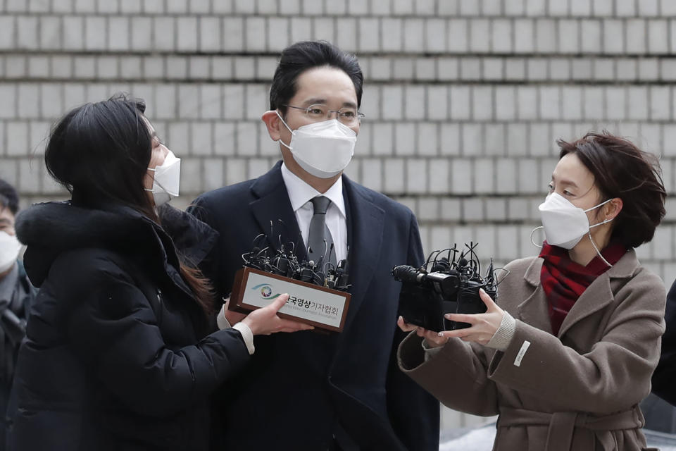 Samsung Electronics Vice Chairman Lee Jae-yong, center, is questioned by reporters upon his arrival at the Seoul High Court in Seoul, South Korea, Monday, Jan. 18, 2021. Samsung scion Lee Jae-yong will not appeal a court ruling that sentenced him to two and a half years in prison for bribing South Korea's then-president for business favors. (AP Photo/Lee Jin-man)