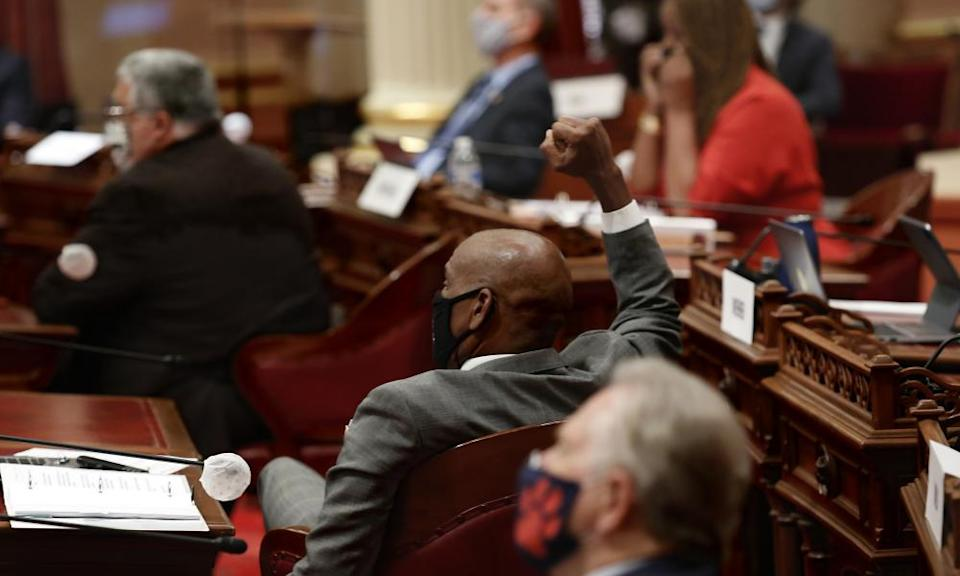 State senator Steve Bradford raises his fist in celebration as the Senate approves a measure to overturn the ban on affirmative action on the November ballot.