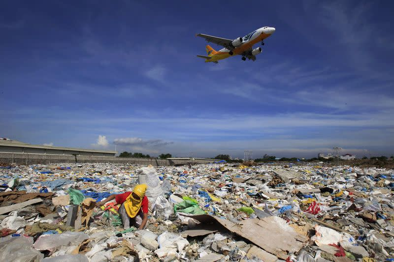 File photo of aircraft flying overhead as a person rummages for recyclables at a garbage dumpsite in Paranaque city