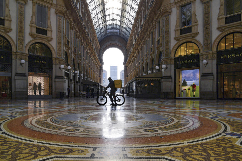 FILE - In this Nov. 6, 2020 file photo, a food delivery rider pushes his bicycle inside the Vittorio Emanuele shopping arcade in Milan, Italy. Italy is cracking down on bike delivery service companies, with one Milan prosecutor saying the riders, most of them immigrants, are practically treated like slaves. Milan prosecutors on Wednesday told a news conference that four delivery companies in Italy have been given 90 days to improve their treatment of riders. (Gian Mattia D'Alberto/LaPresse via AP)