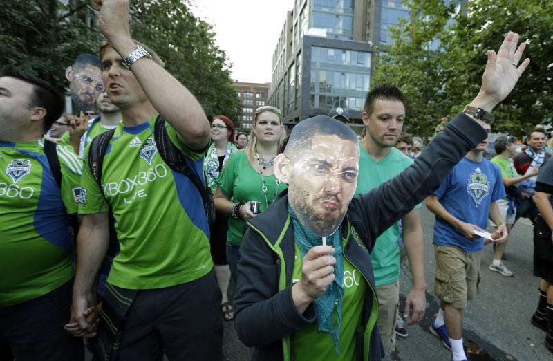 """Seattle Sounders fans carry photos of Clint Dempsey, captain of the United States Mens National Team, as they take part in the traditional """"March to the Match,"""" Saturday, Aug. 3, 2013, prior to a MLS soccer match between the Sounders and FC Dallas in Seattle. Dempsey previously played for Tottenham Hotspur in the English Premier League and reports have linked him to joining the Seattle Sounders. (AP Photo/Ted S. Warren)"""