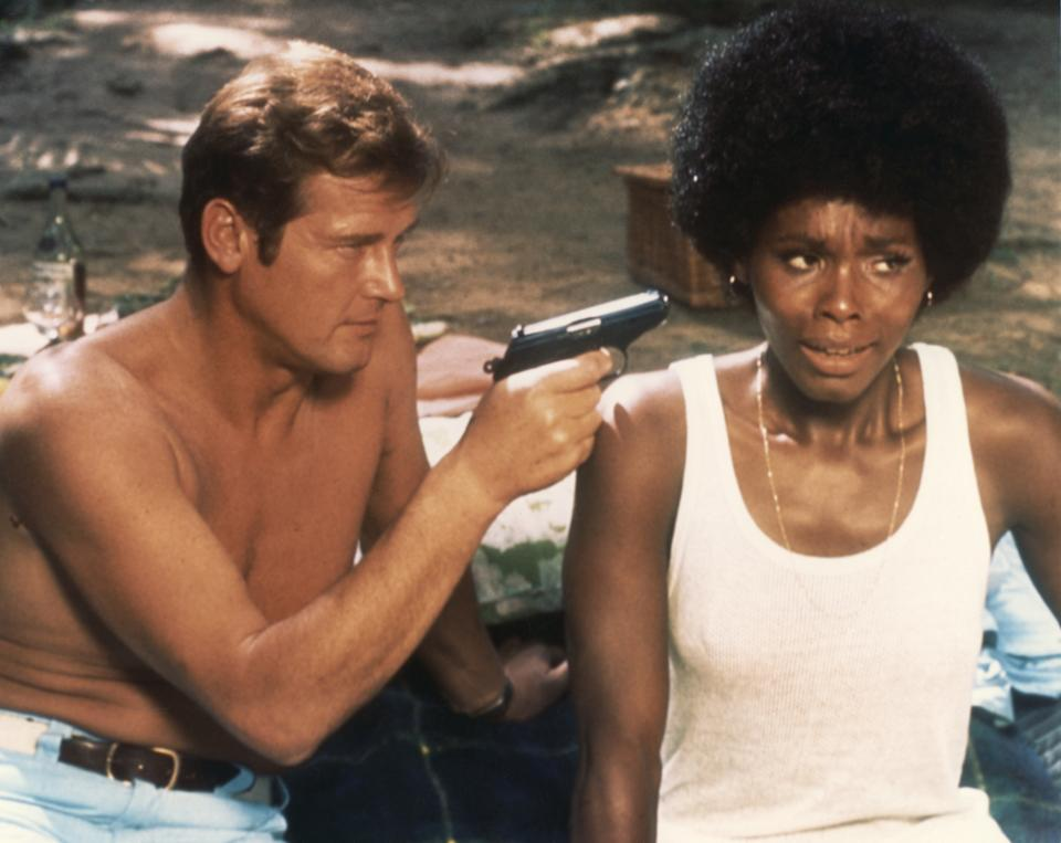 Actor Roger Moore and actress Gloria Hendry on the set of