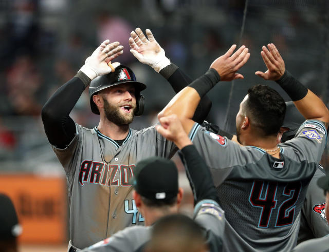 Arizona Diamondbacks' Christian Walker, left, celebrates as he returns to the dugout after hitting a solo-home run in the ninth inning of a baseball game against the Atlanta Braves, Tuesday, April 16, 2019, in Atlanta. (AP Photo/John Bazemore)