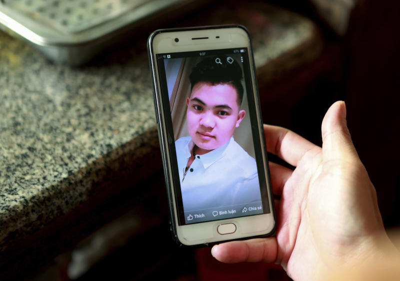 FILE - In this Oct. 28, 2019 file photo, Hoang Thi Ai, mother of Hoang Van Tiep, who is feared to be among the England truck dead, hold a phone showing a photo of Tiep in Dien Thinh village, Nghe An province, Vietnam. Ten teenagers were among the 39 Vietnamese found dead in a truck container in southeast England last month, local police said Friday, Nov. 8 while relaying for the first time details of those who died. Two of the dead were only 15, while the oldest was 44. Some 20 of the victims came from one province — Nghe An in north central Vietnam, around 200 kilometers (120 miles) south of Hanoi. Hoang Van Tiep was among the dead. (AP Photo/Hau Dinh)