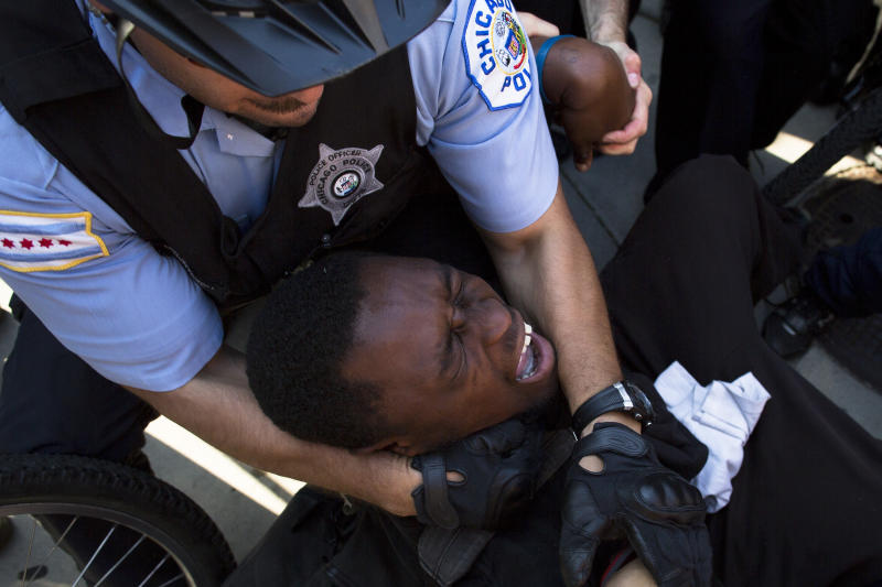 A NATO protestor is arrested after refusing to let go of a police bicycle, Saturday, May 19, 2012, in Chicago. Security has been high throughout the city in preparation for the NATO summit, where delegations from about 60 countries will discuss the war in Afghanistan and European missile defense. (AP Photo/John Minchillo)