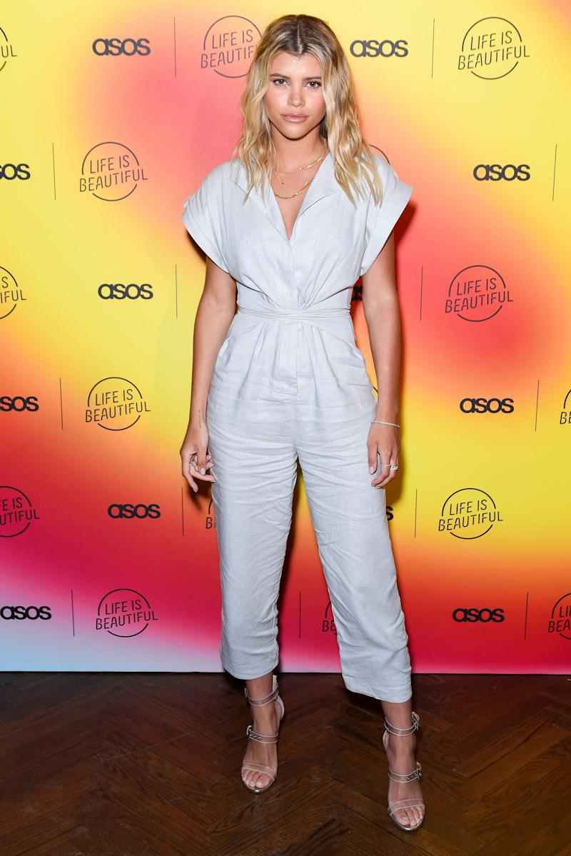 Sofia Richie poses wearing a white jumpsuit