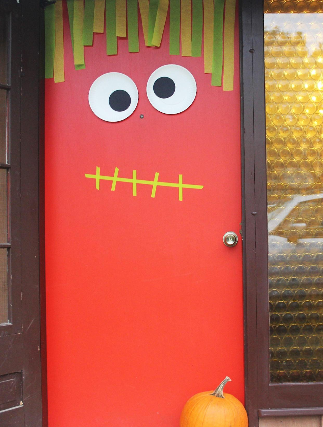 Bright red door with cutout eyes and a strip of paper hanging down like hair
