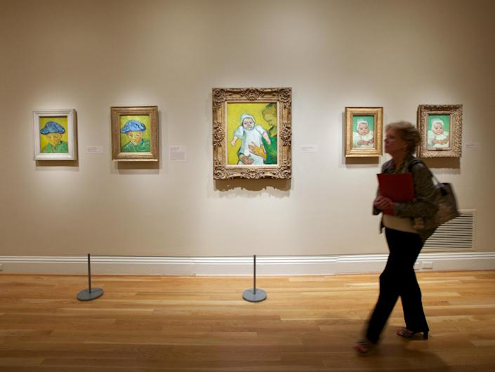 """In this Oct. 8, 2013 photo, a woman walks past Vincent van Gogh pieces, including """"Portrait of Camille Roulin,"""" left, and """"Portrait of Marcelle Roulin,"""" right, on display at The Phillips Collection in Washington. In the midst of the shutdown of federally funded museums, the private Phillips Collection is launching the first major exhibition of Vincent van Gogh's artwork in Washington in 15 years. (AP Photo/Molly Riley)"""