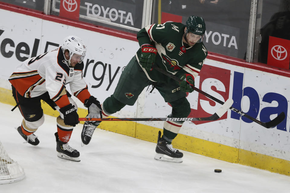 Minnesota Wild's Carson Soucy (21} goes after the puck against Anaheim Ducks' Sam Steel (23) during the first period of an NHL hockey game Friday, May 7, 2021, in St. Paul, Minn. (AP Photo/Stacy Bengs)