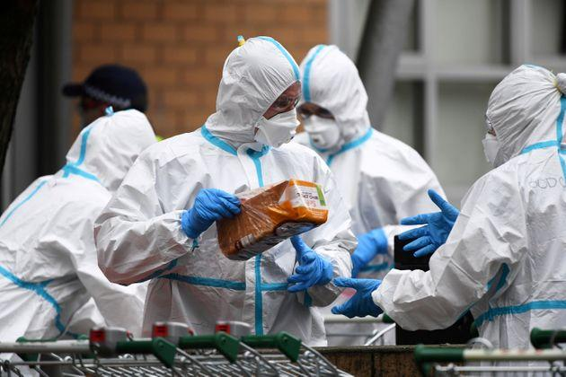 Firefighters dressed in personal protective equipment prepare to distribute food throughout a public housing tower, locked down in response to an outbreak of the coronavirus disease (COVID-19), in Melbourne, Australia, July 7, 2020.
