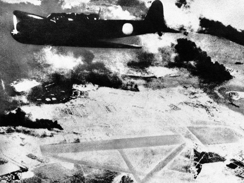 A Japanese plane flying over Pearl Harbor as black smoke rises from the area.