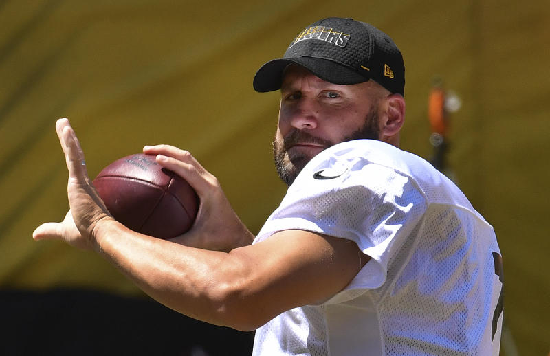 Ben Roethlisberger drops back to pass wearing a white jersey and black ballcap.