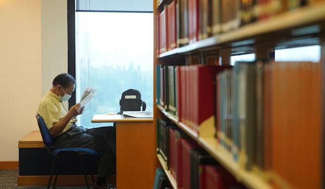 An elderly man catches up with current events at the Hong Kong Central Library. Photo: Winson Wong