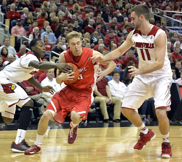 Cornell's Jake Matthews, center, attempts to fight his way through the defense of Louisville's Terry Rozier, left, and Luke Hancocok during the first half of an NCAA college basketball game on Friday, Nov. 15, 2013, in Louisville, Ky. (AP Photo/Timothy D. Easley)