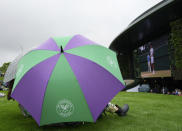 Spectators shelter under an umbrella during a rain delay on day one of the Wimbledon Tennis Championships in London, Monday June 28, 2021. (AP Photo/Alberto Pezzali)
