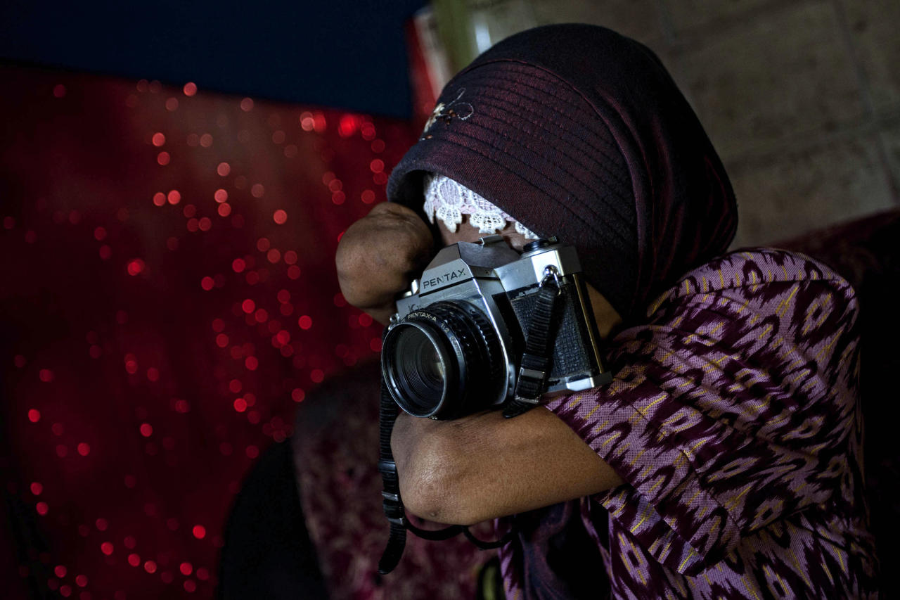 PURWOREJO, INDONESIA - MARCH 13:  Armless professional photographer Rusidah, 44, takes a photograph as she carries out camera maintenance on March 13, 2012 in Purworejo, Indonesia. Rusidah shoots weddings and parties and has a small studio at home in the village of Botorejo, Bayan District, Purworejo, Central Java where her husband and son also reside. She has been in the photography business for nearly 20 years.  (Photo by Ulet Ifansasti/Getty Images)