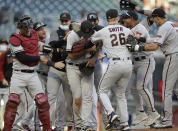 Arizona Diamondbacks pitcher Madison Bumgarner, center, is congratulated by teammates after pitching a 7-inning no hitter against the Atlanta Braves, the second baseball game of a double header, Sunday, April 25, 2021, in Atlanta. (AP Photo/Ben Margot)