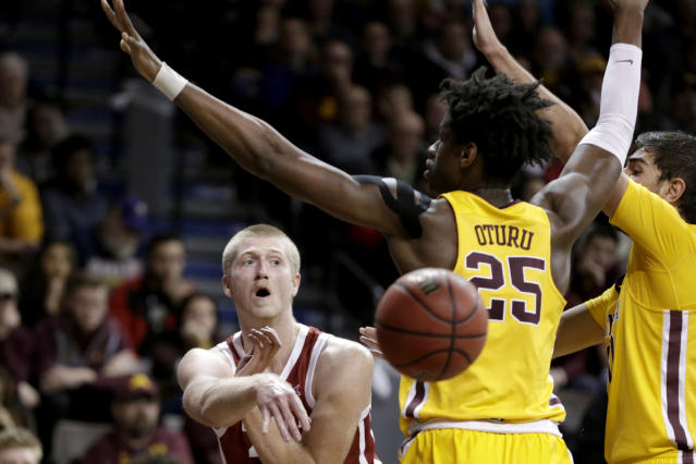 Oklahoma's Brady Manek, left, passes the ball around Minnesota's Daniel Oturu (25) during the first half of an NCAA college basketball game in Sioux Falls, S.D., Saturday, Nov. 9, 2019. (AP Photo/Nati Harnik)