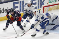 Columbus Blue Jackets' Alexandre Texier, left, of France, looks for an open shot as Tampa Bay Lightning's Mikhail Sergachev, center, of Russia, and Callan Foote defend during the first period of an NHL hockey game Saturday, Jan. 23, 2021, in Columbus, Ohio. (AP Photo/Jay LaPrete)