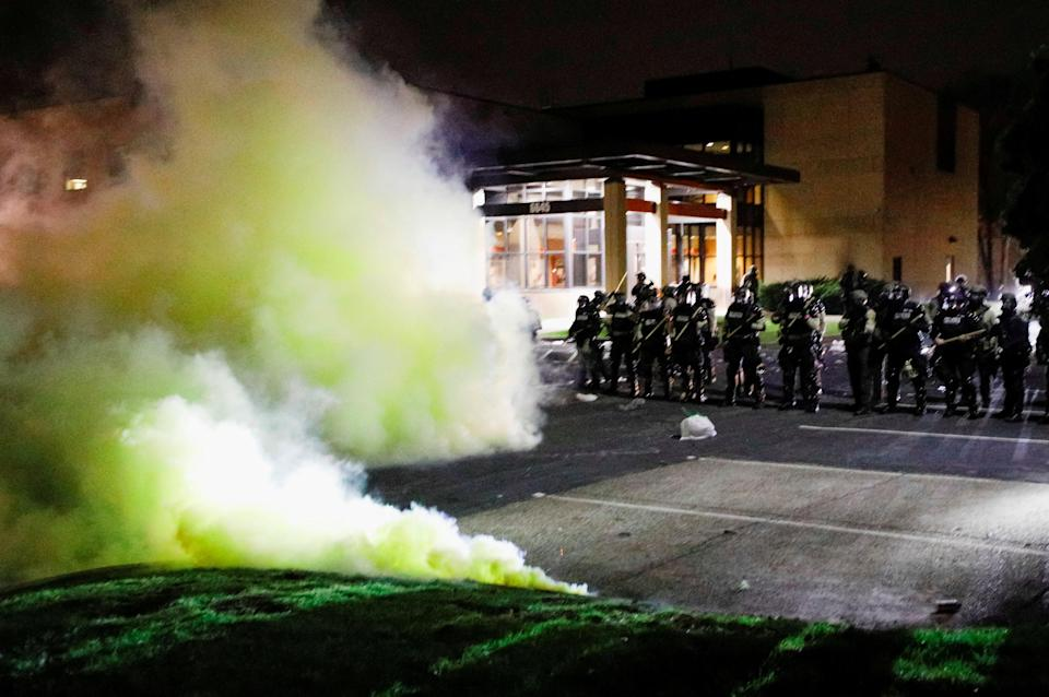 Protests: Tear gas is seen as officers stand guard outside Brooklyn Center Police Department (REUTERS)