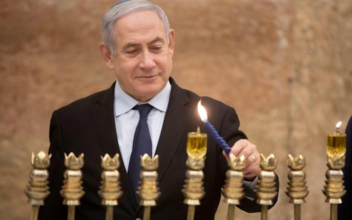 Israeli Prime Minister Benjamin Netanyahu, lights a Hanukkah candle at the Western Wall