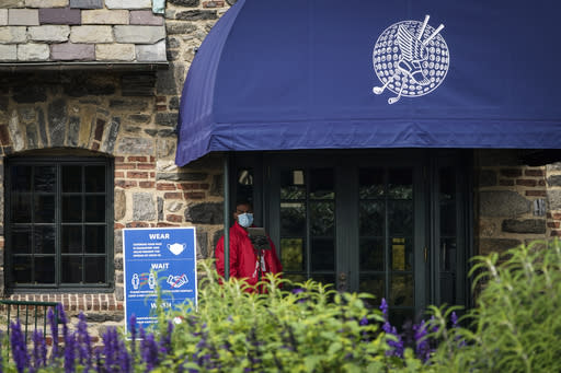 A door attendant wears a protective mask outside the clubhouse on the second day of practices before the U.S. Open Championship golf tournament at Winged Foot Golf Club, Tuesday, Sept. 15, 2020, in Mamaroneck, N.Y. (AP Photo/John Minchillo)