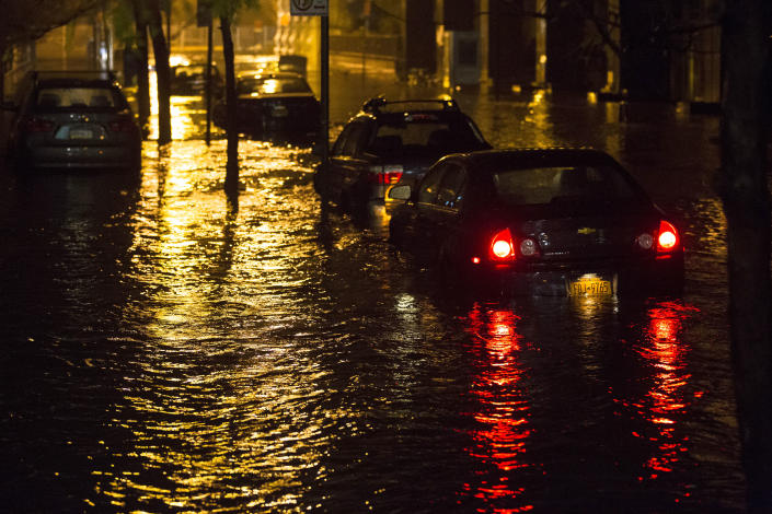 Vehicles are submerged during a storm surge near the Brooklyn Battery Tunnel, Monday, Oct. 29, 2012, in New York. Superstorm Sandy zeroed in on New York's waterfront with fierce rain and winds that shuttered most of the nation's largest city Monday, darkened the financial district and left a huge crane hanging off a luxury high-rise. (AP Photo/ John Minchillo)