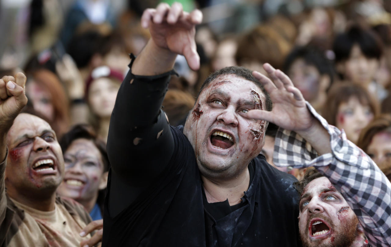 Former sumo grand champion Akebono, center, and other participants in zombie costumes, perform during a Halloween event at Tokyo Tower in Tokyo, Thursday, Oct. 31, 2013. (AP Photo/Shizuo Kambayashi)