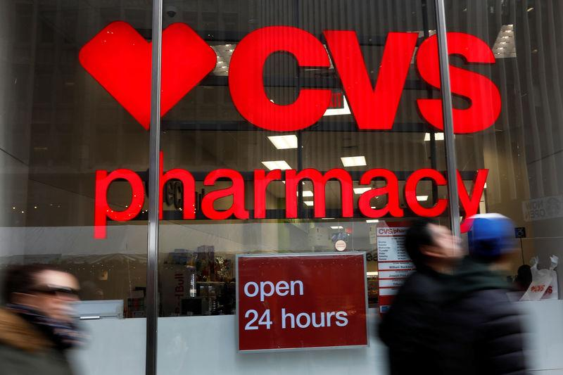 People walk by a CVS Pharmacy store in the Manhattan borough of New York City