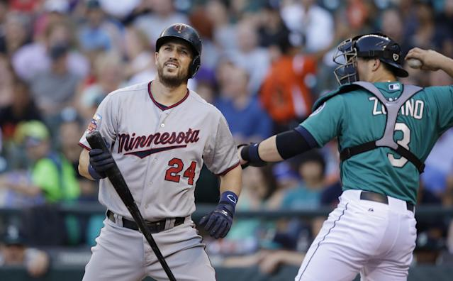 Minnesota Twins' Trevor Plouffe, left, turns toward the dugout after striking out as Seattle Mariners catcher Mike Zunino returns the ball to the mound in the first inning of a baseball game Monday, July 7, 2014, in Seattle. (AP Photo/Elaine Thompson)