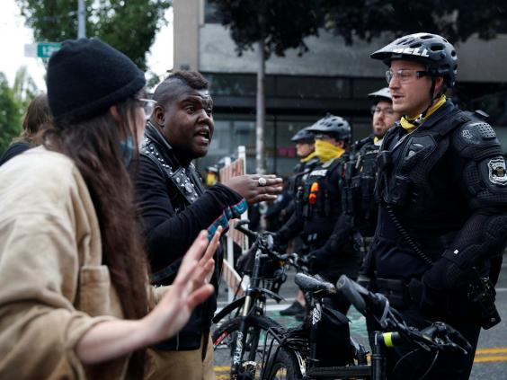 Protesters talk to Seattle police officers on 1 July (REUTERS)