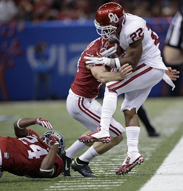 Oklahoma running back Roy Finch (22) is stopped by Alabama linebacker Matt Tinney (43) and defensive back Geno Smith (24) during the second half of the NCAA college football Sugar Bowl in New Orleans, Thursday, Jan. 2, 2014. (AP Photo/Patrick Semansky)