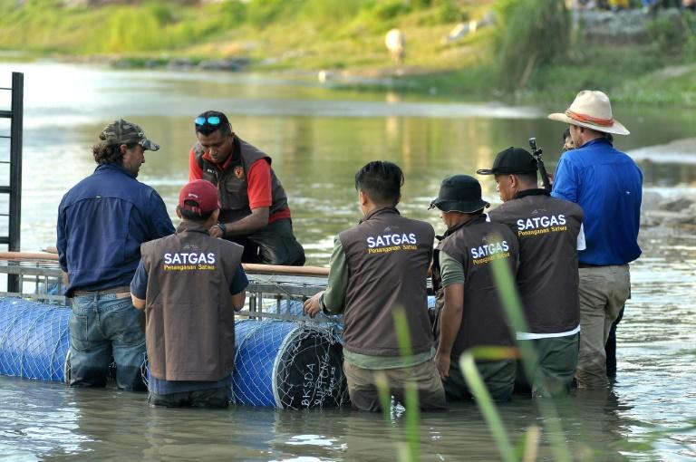 Australian crocodile wranglers Matthew Nicolas Wright (right) and Chris Wilson (left) directing the lndonesian team in setting the trap in the river in Palu (AFP Photo/Olagondronk)