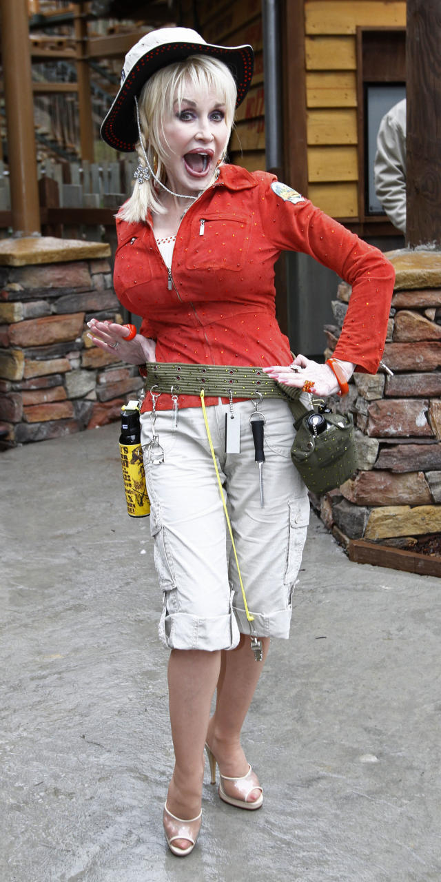 Dolly Parton poses for a photograph by her latest attraction, Adventure Mountain, during the 25th anniversary celebration of the Dollywood Theme Park, Friday, March 26, 2010 in Pigeon Forge, Tenn. (AP Photo/Wade Payne)