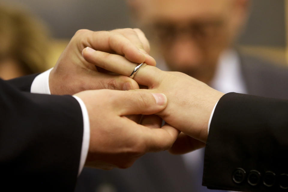 "FILE - In this May 21, 2015 file photo, Mauro Cioffari, left, puts a wedding ring on his partner Davide Conti's finger as their civil union is being registered by a municipality officer during a ceremony in Rome's Campidoglio Capitol Hill. Pope Francis endorsed same-sex civil unions for the first time as pope while being interviewed for the feature-length documentary ""Francesco,"" which premiered Wednesday, Oct. 21 2020 at the Rome Film Festival. (AP Photo/Gregorio Borgia, file)"
