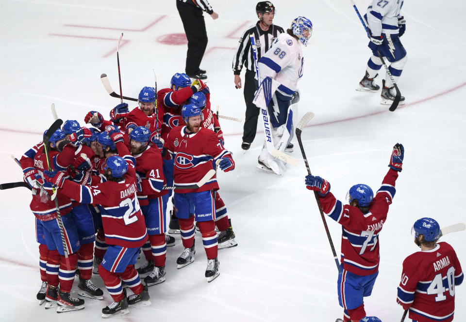 Tampa Bay Lightning goaltender Andrei Vasilevskiy (88) skates off the ice as members of the Montreal Canadiens celebrate a goal by Josh Anderson during overtime of Game 4 of the NHL hockey Stanley Cup final in Montreal, Monday, July 5, 2021. (Paul Chiasson/The Canadian Press via AP)