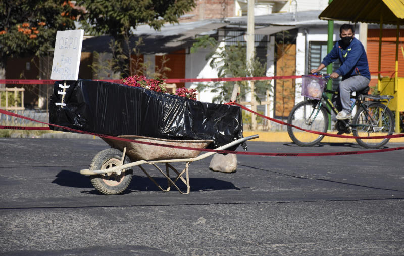A coffin wrapped in plastic containing the remains of an unidentified men, who died last week, sits on a wheelbarrow in the middle of a street, placed there by his family to draw attention of the authorities to show that his remains are yet to be collected, in Cochabamba, Bolivia, Saturday, July 4, 2020. Funeral services in Cochabamba are overwhelmed and bodies are piling up, waiting for cremation or burial, as new coronavirus cases rapidly multiply in one of the epicenters of the pandemic in Bolivia. (AP Photo/Dico Soliz)