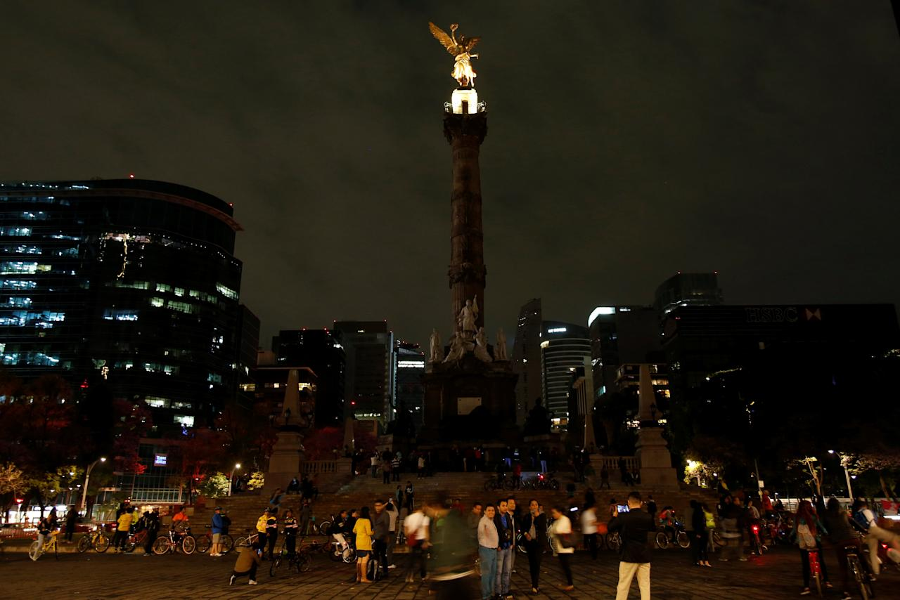 "People stand by ""Angel de la Independencia"" monument after the lights were turned off for Earth Hour in Mexico City, Mexico, March 25, 2017. REUTERS/Ginnette Riquelme"