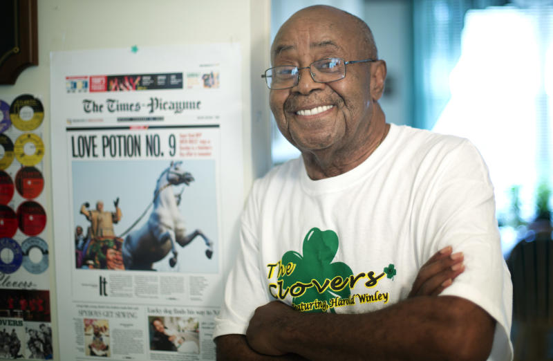 "Harold Winley, who performed ""Love Potion No. 9"" and other hits with the band The Clovers in the 50s, stands by the front page of a New Orelans newspaper that used his song as a headline after the Saints won a football championship posing for photos Friday, Aug. 2, 2013 in Lauderdale Lakes, Fla. home. The 80-year-old says a splinter group is trying to keep him from performing using the band's name. (AP Photo/J Pat Carter)"