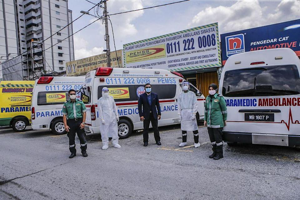 Paramedic EMS Services Sdn Bhd general manager and chief paramedic Faizal Nurdin (centre) and his staff pose for the camera at the company's headquarters in Kuala Lumpur July 5, 2021. — Pictures by Hari Anggara