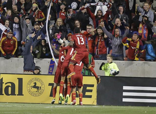 CORRECTS SCORE - Real Salt Lake players celebrate with Real Salt Lake defender Chris Schuler after he scored in overtime during the second leg of the MLS Western Conference semifinal against the Los Angeles Galaxy Thursday, Nov. 7, 2013, in Sandy, Utah. Real Salt Lake won 2-0. (AP Photo/Rick Bowmer)