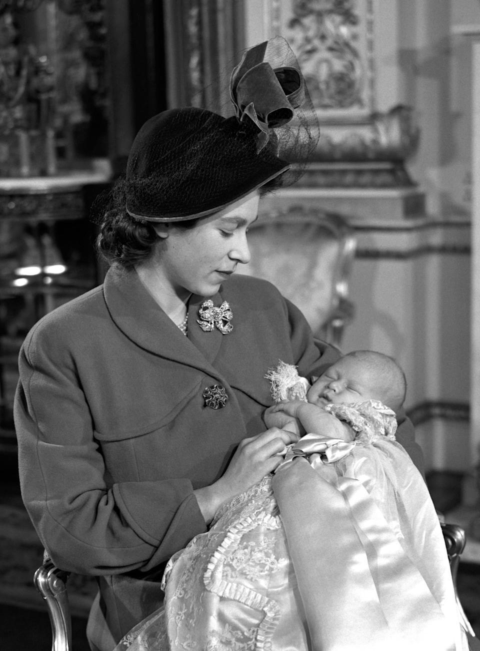 <p>Princess Elizabeth holds her son Prince Charles after his Christening ceremony in Buckingham Palace (PA Archive) </p>