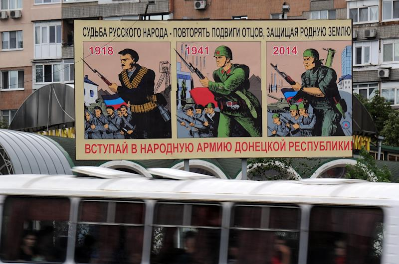 "A bus rides by a giant poster reading ""The fate of the Russian people, to repeat the feats of fathers : defend their native land"" in Donetsk, on July 15, 2014"