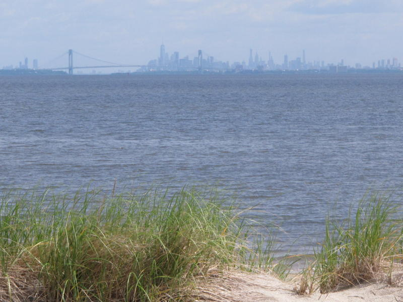 In this June 3, 2019 photo the New York City skyline is in the background of the Raritan Bay as seen from Middletown, N.J.  New Jersey environmental officials are due to decide Wednesday, June 5 on key permits for a nearly $1 billion pipeline that would bring natural gas from Pennsylvania through New Jersey, out into Raritan Bay and into the ocean before reaching New York and Long Island. (AP Photo/Wayne Parry)