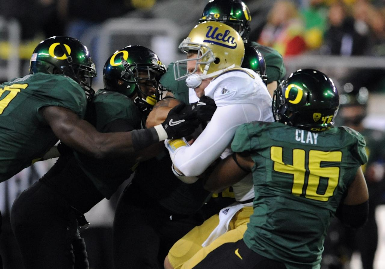 EUGENE, OR - DECEMBER 02 : Quarterback Kevin Prince #4 of the UCLA Bruins is tackled by a host of Oregon Ducks including linebacker Michael Clay #46 of the Oregon Ducks in the first quarter of the Pac-12 Championship game against  the UCLA Bruins at Autzen Stadium on December 2, 2011 in Eugene, Oregon. (Photo by Steve Dykes/Getty Images)
