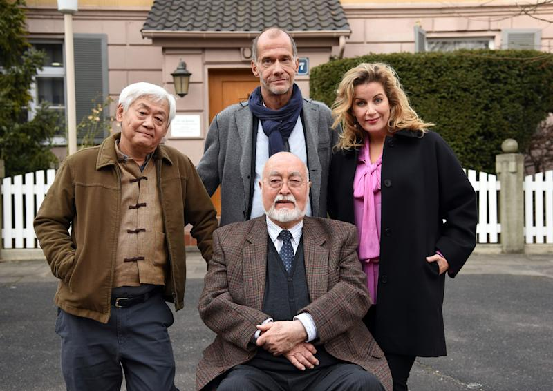 """06 March 2018, Germany, Cologne: The actors Ludwig Haas (Dr. Dressler, front), Amorn Surangkanjanajai (L-R, Gung Pham Kien), Georg Uecker (Carsten Floeter) and Alexa Maria Surholt (Sarah Marquardt, L-R) look into the camera during a photo session for the television series """"Lindenstrasse"""". Photo: Henning Kaiser/dpa (Photo by Henning Kaiser/picture alliance via Getty Images)"""