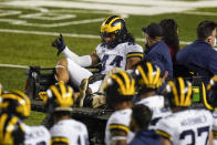Michigan's Cameron McGrone (44) gestures to teammates as he is carted off the field after being injured during the first half of the team's NCAA college football game against Rutgers on Saturday, Nov. 21, 2020, in Piscataway, N.J. (AP Photo/Frank Franklin II)
