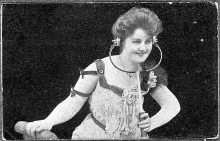 A young woman of the early 20th century listening to Electrophone through headphones